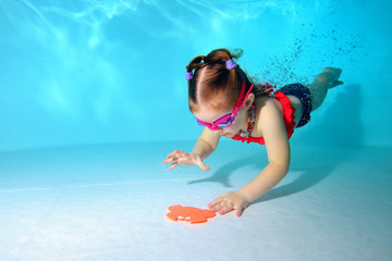 Little girl underwater dives to the bottom of the pool for a toy. Portrait. Shooting under water. Horizontal orientation