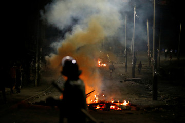 Riot police watch as protesters stand near barricades set on fire by opposition supporters in the slum area of Mathare in the capital Nairobi