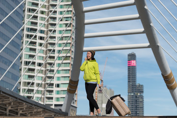 Happy female tourist with suitcase while walking in city building, Travel concept