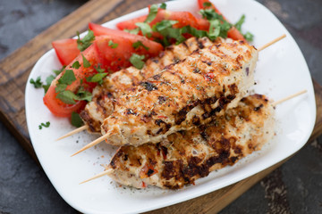 Closeup of lula kebabs with chicken and sliced red tomatoes on a white tray, studio shot