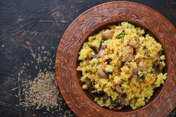 Clay plate with pilaf on a dark brown stone background, horizontal shot with space, view from above