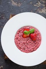 White plate with strawberry risotto over brown stone background, vertical shot, above view