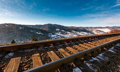 railroad in mountains with snowy slopes. lovely transportation scenery on winter sunny day