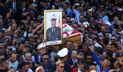 Relatives and colleagues carry the coffin and the picture of Tunisian police officer Riadh Barrouta who  died after a knife attack near the parliament building in Tunis