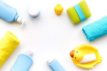 Bath accessories for kids. Yellow rubber duck, soap, sponge, brushes, towel on white background top view copyspace