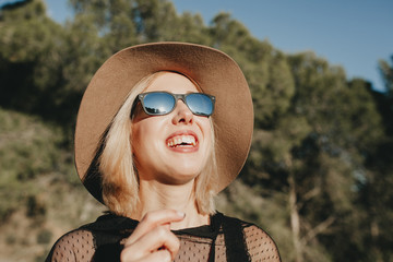 Close up portrait of happy blonde woman with hat and sunglasses laughing in nature with sunlight in her face.