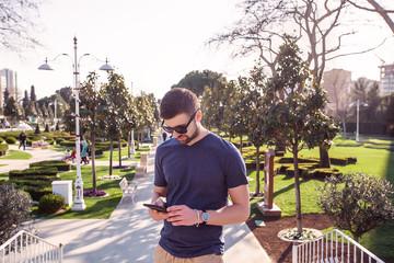 Man in sunglasses on park stairway looking down at smartphone