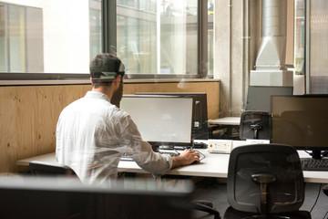 Rear view of man in office using desktop computer