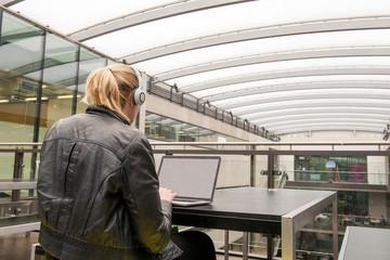 Rear view of woman on mezzanine of office building using laptop