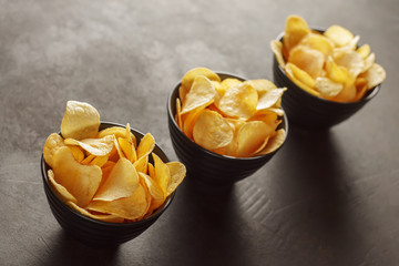 Three black bowls with crunchy potato chips on the table.