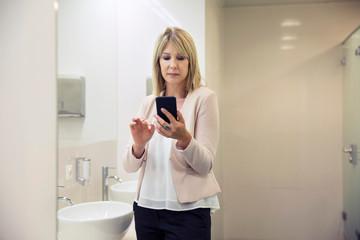 Woman using smartphone in bathroom