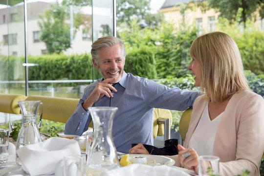 Smiling couple al fresco dining at restaurant