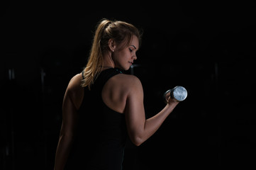 Fit sporty woman exercising with dumbbell. Fitness female posing on black background. Fitness and healthy lifestyle concept.