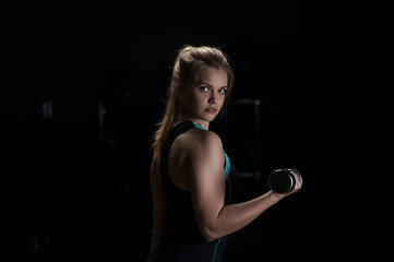 Confident sporty young woman posing with weights. Fitness and sports concept.