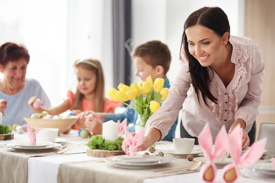 Woman and family preparing place settings at easter dining table