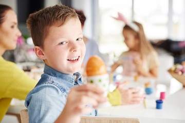 Portrait of boy holding painted hard boiled easter egg at table