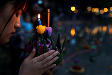 A girl prays before casting a krathong into a pond at a public park during the Loy Krathong festival in Bangkok