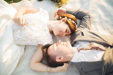 Wedding, beautiful romantic bride and groom kissing, embracing at sunset