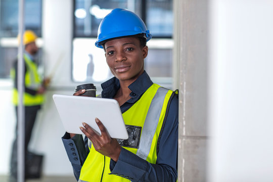Woman with hard hat and hi viz jacket using digital tablet
