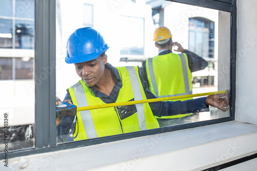 woman in hard hat and high viz jacket measuring window stock photo