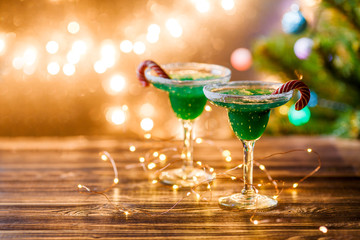 Christmas picture of two wine glasses with green cocktail, caramel sticks and garland