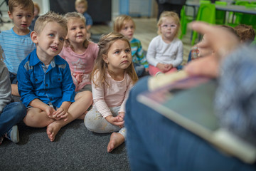 Young children sitting on carpet in classroom, listening to teacher at front of class