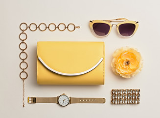 Fashion. Woman Accessories Set. Trendy Gold Watch, Summer Sunglasses, Glamour fashion Yellow Clutch. Flower. Flat lay. Luxury Stylish Spring lady. Pastel Color