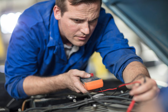 Car mechanic testing car engine in repair garage