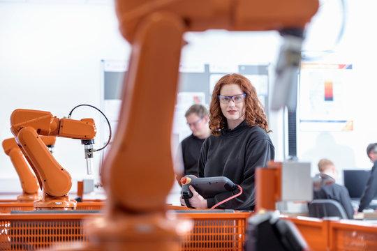 Portrait of female robotics apprentice using test industrial robots in robotics facility