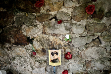 The photograph of a Socialist militia member killed during the Spanish Civil War is pinned on a wall next to roses at Derio cemetery on All Saints Day, near Bilbao