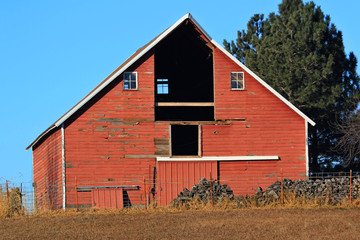 Red Barn with early morning sun peaking thru into the hay loft