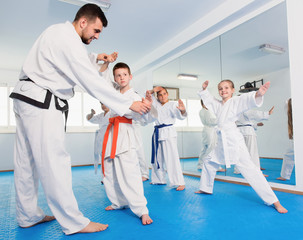 Children training with coach during karate class