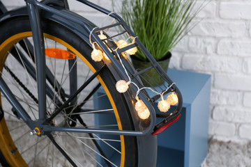 Black bicycle with glowing garland indoors