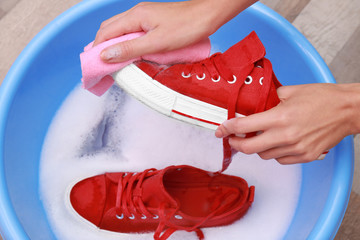 Woman washing sneakers with rag over plastic basin, closeup