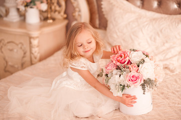 Smiling baby girl 3-4 year old holding flowers wearing white stylish dress sitting in bed. Happy birthday.