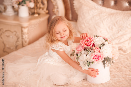 fd9f552852 Smiling baby girl 3-4 year old holding flowers wearing white stylish dress  sitting in