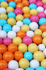 Shiny sugar coated round chocolate balls as background. Candy bonbons multicolored texture. Round candies sweets pattern concept. Food photo studio photography. Candy background Choco dragee.
