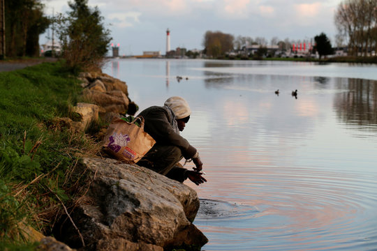 A Sudanese migrant brushes his teeth on the banks of a channel near the port of in Ouistreham