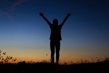 Silhouette of a standing with her hands up as the sign of happiness