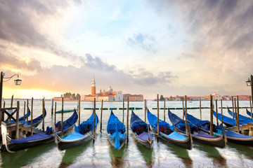 Gondolas with San Giorgio Maggiore church at sunrise in Venice, Italy