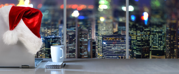 Laptop on table with Santa Claus hat in office with panoramic night view of modern downtown skyscrapers at business district