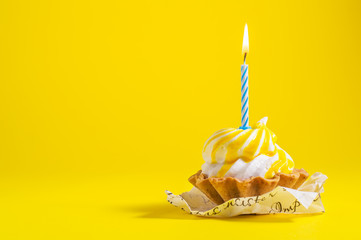 Tasty Birthday cupcake with candle on yellow background with copy space. Delicious muffin on color background.