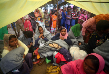 Rohingya refugees, who were on a boat travelling from Myanmar that capsized at Bailakhali beach, wait to transported to a refugee camp from the beach, near Cox's Bazar