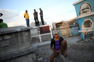 A woman sits next to graves during celebrations at a cemetery in Port-au-Prince