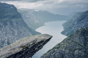 Famous trekking destination and rock formation Trolltunga in Odda, Norway, during the rainy day with the clouds in the sky