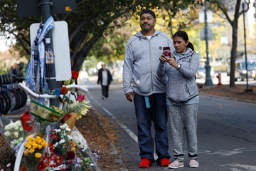 People pause to take a photo by a ghost bike, an existing roadside memorial, that is now used to remember the victims of the Tuesday's attack alongside a bike path at Chambers Street in New York City, in New York