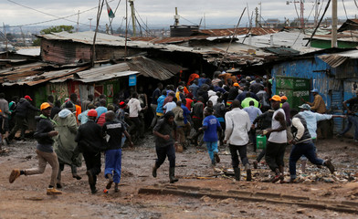 Protesters run as riot police attempt to disperse supporters of Kenyan opposition leader Raila Odinga in Kibera slums of Nairobi