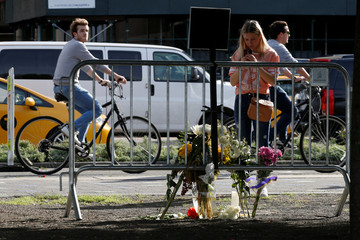 People stop to look at memorials along a bike path to remember the victims of the New York October 31 attack, in New York