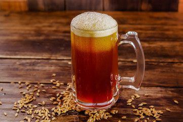 Indoor view of glass of beer with wheat in the base on a wooden table on a blurred background