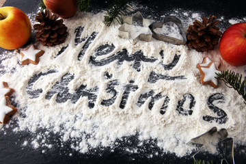 Christmas composition. Merry christmas text made with flour on black background and cookies.